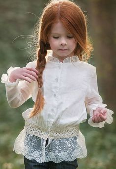 .beautiful little girl with red hair & she's wearing a pretty lacey long-sleeve blouse.