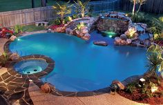 LED lit free form swimming pool with rock waterfall and spa