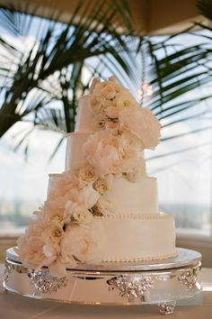 The cake will have a cascade of ivory peonies, blush roses, and blush spray roses
