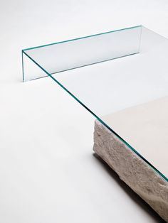 TERRALIQUIDA design Claudio Silvestrin   Low table composed of a parallelepiped Limestone stone with a monolithic appearance and an element in tempered 15 mm. thick glued 45° transparent extralight glass that rests on it. The stone parallelepiped has the sides in a split-face finish, whereas the top is flamed. The materiality, the gravity and the solidity of the stone juxtapose the lightness, the purity and the ethereality of the glass.