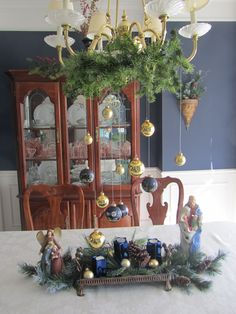 hang your favorite ornaments from the chandelier with fishing twine.  put greenery around the bottom of chandelier and  voila, a beautiful decoration for your dining room table. I decorated the table with greenery and a couple nativities too.