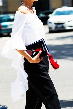A white Ellery ruffle top is paired with black trousers and a pearl statement necklace