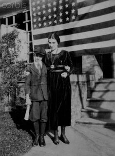 Brother and sister stand in front of the American flag-draped Indiana home on November 11, 1918 after the announcement that an armistice had been signed to end World War I.