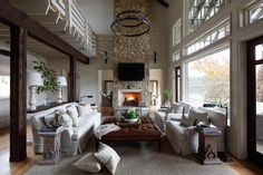 Beautiful two-story country living room boasts a tall stone fireplace lined with a flat screen television placed over a white beveled fireplace mantle lit by Suzanne Kasler 1 Light Alice Wall Sconces.