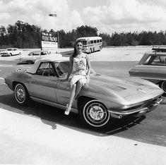 Girl sits on the hood of a 1963 Corvette convertible outside Weeki Wachee springs in Florida
