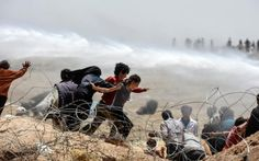 Syrian refugees run away as Turkish soldiers use water cannon to move them away…