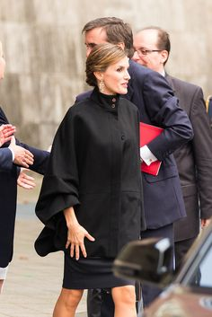 Queen Letizia of Spain can't wait until Winter to show off her amazing new coats; that's why she wore one of them in early October while attending the opening of the Zurbarán in Düsseldorf, Germany. The royal dressed in an amazing high-collar, cape-shaped black topper and called attention to the button details on her neckline with her hair pulled up in a bun and shiny drop earrings.