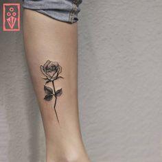 Tatuagem criada por Matheus Sari de Curitiba.  Flor delicada em preto e cinza na perna.
