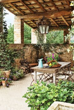 Outdoor patio with rustic table and chairs surrounded by potted plants // Italian design