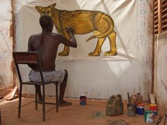 """Cyprien Tokoudagba   Cyprien is painting Agassou ,the God of the Panther, in his family compound. Cyprien Tokoudagba , born in 1939, lives and works in Abomey, Benin. He his an initiate of vodun Tôhôssou, god of the water.He began his artwork by adorning the walls of vodun temples, and later restored the """"bas-reliefs"""" of the royal palaces of Abomey. He began using canvas on commissions in 1989.His works represent symbols & deities of Vodun as well as mottos and emblems of the Abomey Kings."""