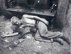 A tired Marine soldier and dog sleep on a bed of rocks during the invasion of Okinawa, May or June 1945.