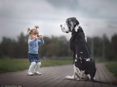 Photographer Andy Seliverstoff, 58, spent four months taking pictures in St. Petersburg, Russia, for a book called'Little Kids and Their Big Dogs'. The photos show children under 2ft with giant dogs.