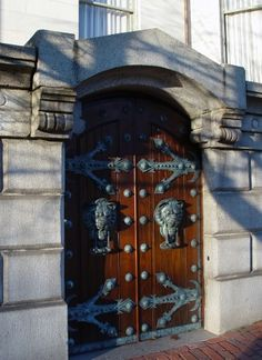 Wooden doors on Beacon Hill in Boston, Massachusetts, with large lion's head door knockers, large hinges, and rivets set in a ornated cement wall