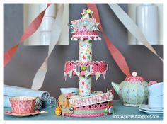 Look at this adorable 3-tiered cupcake stand Thienly created using HAPPY BIRTHDAY TO YOU KIT, ROSIE'S RIBBON STRIPS COLLECTION, STARS AND STRIPES KIT.  The teapot and cup are from the TEA FOR YOU AND ME KIT.  Just too cute!  Strong enough to hold cupcakes and candy!