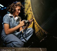 A female riverter at work on a bomber at the Consolidated Aircraft factory in Fort Worth