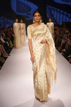 A stunning white and gold saree with zari detailing and weaves.
