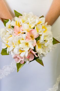 Photo about A beautiful frangipani flower wedding bouquet in front of a white wedding dress. Image of artistic, pink, bouquet - 10314361 Plumeria Bouquet, Frangipani Wedding, Plumeria Flowers, Beach Wedding Flowers, Flower Bouquet Wedding, Tropical Flowers, Floral Wedding, Tropical Wedding Bouquets, Bridal Bouquets