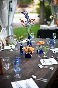 Blue glass bottles and fall flowers. Photography by revertphoto.com,