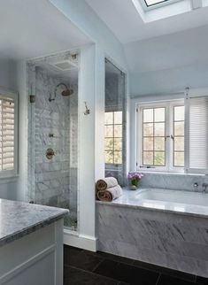 blue gray marble bathroom with slate floors standalone shower and tub and skylight