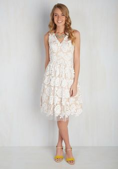 Make extraordinary moments all the more memorable by wearing this elegant, pocketed dress. Featuring a stirring V-neckline, a darted bust, and a tulle overlay of delicate, white lace roses, this beautiful mid-length frock will win hearts no matter the occasion.