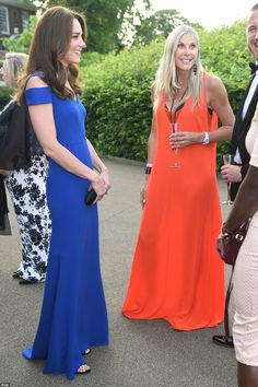 The Duchess chats to guests including one brightly-dressed reveller in a floor-sweeping or...