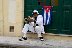 A man plays the trumpet with the Cuban flag behind him. Meet the locals, experience everyday life, and improve your travel photography on a cultural tour with Ralph Velasco and PhotoEnrichment Adventures. Find out about our upcoming tours at https://photoenrichment.com
