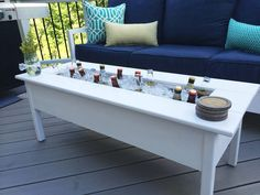 An outdoor cooler coffee table has a removable center board to cover the cooler when it's not in use.