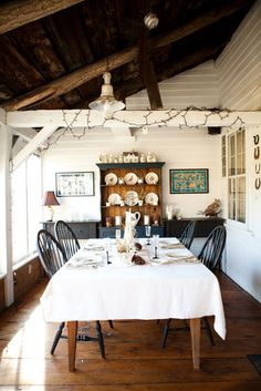 Black and white farmhouse dining room with white wood siding and exposed beams.