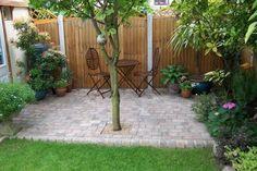 Idee für eine kleine Terrasse im Garten aus Pflastersteinen und Metallstühlen