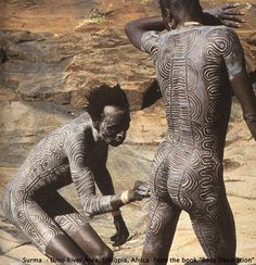 Body Art -- In preparation for the stick fighting competitions, Surma men cover their skin with chalk mixed with water and then make line patterns through the chalk ...