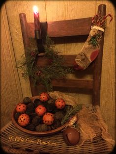 Sweet little stocking a friend made, juniper wreath and a early looking candle holder. Antique wooden bowl filled with studded oranges, English walnuts a sprig of greens sitting atop a old chair. By Ye Olde Crow Primitives