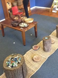 Natural loose part play indoors: mat (burlap), tree blocks, stumps, glass beads.     Integrate stumps: seating