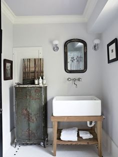 Place a cabinet, table, or stool in the bathroom to guarantee visitors won't have to balance their Dopp kits on the edge of the sink.