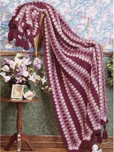 """Shades of Rose Afghan - Classic shades of burgundy and pink bring a romantic glow to this traditional mile-a-minute style design. An interesting texture, artfully combined with stately tassels, offers warmth and decorative appeal.  size: 61 x 79"""" (appx)  Skill level: Average  Designed by Ernestine Barff  free pdf from freepatterns.c0m"""
