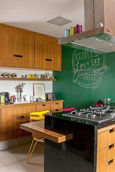 Móveis revestidos de lâmina de freijó dividem o espaço com um imponente fogão cooktop e a parede de tinta lousa, perfeita para deixar os recados em giz