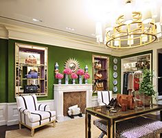Tory Burch - Incredible closet with deep crown molding with gold trim over moss green upper walls and wainscoting clad lower walls alongside hardwood floors layered with a braided sisal rug.