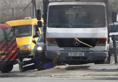 A truck driven by a Palestinian man runs over an Israeli man as a stick he was wielding is thrown into the air at Fawar junction near the West Bank city of Hebron, Oct. 20, 2015. The Israeli, who later died, had gotten out of his car after Palestinian demonstrators threw stones at it and began to hit passing Palestinian cars with the stick.