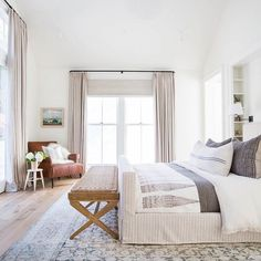 Neutral master bedroom design with a white, beige, and gray color scheme featuring a woven seat wood bench at the foot of the bed and a large patterned area rug - Neutral Home Ideas & Decor