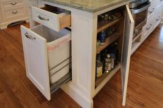Multi-functional kitchen island with tons of storage. Hidden pull-out garbage can is installed at one end of kitchen island whilst mini spice pantry is installed next to built-in microwave nook.