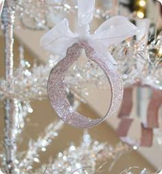 Cover a cookie cutter in glitter to turn them into real ornaments! To create, paint craft glue onto cookie cutter then shake inside a plastic bag filled with glitter. Allow to dry overnight then secure ribbon on top with hot glue.