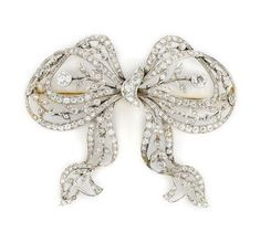 A belle époque diamond bow brooch, circa 1905 composed of old European and single-cut diamonds, estimated total diamond weight: 3.75 carats; mounted in platinum; length: 2 1/4in.