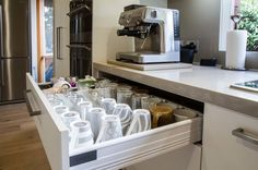 You'll never regret a cup drawer — it's so much easier than digging in an overhead cupboard. Make sure it is deep enough for your tallest mugs, about 7 or 8 inches, storing them upside down to protect their rims. | Kitchen by The Kitchen Design Centre