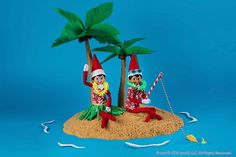 Two elves, dressed in Hawaiian attire, enjoy an island scene The Elf, Elf On The Shelf, Elves At Play, Mini Palm Tree, Kids Punch, Mini Flags, Yellow Paper, Peppermint Candy, Paper Tape