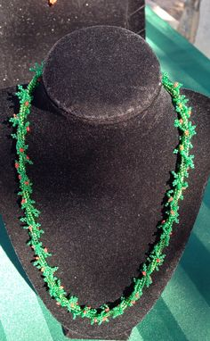 Necklace hand woven Christmas themed. Made to resemble garland and holly.