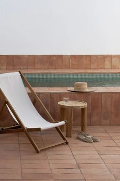 FORESTA's first collection of considered designs - A terracotta swimming pool with easy lounge chair and wooden side table