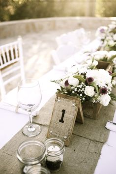 Beautiful rustic wedding table centerpiece using burlap and wood.