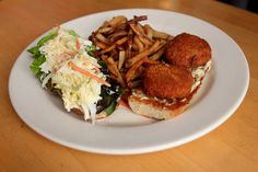 Dungeness Crab Cake Sandwiches: our  house made crab cakes filled with green onions, celery & bacon, pan-fried & served on a potato roll with house made tartar sauce, leaf lettuce & cole slaw