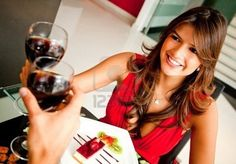 Woman in a romantic dinner celebrating with wine