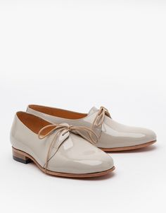 Patent leather round toe oxford by Dieppa Restrepo. Features leather sole and insole, low stacked heel, low cut vamp with extended tongue and lace up overlay.   100% Leather