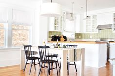 Kitchen with white walls, white light fixture, white cabinets, green tile backsplash, black chairs, white table, and wood floors